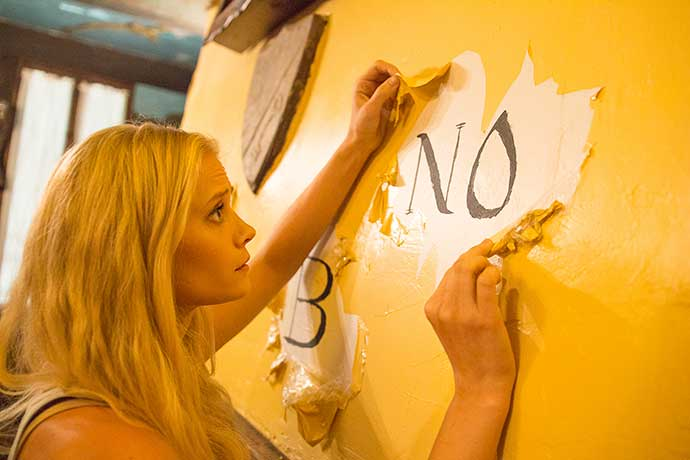 OUIJA-HOUSE-still-6---Carly-Schroeder-discovers-the-Ouija--House